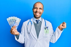 Hispanic adult doctor man wearing medical uniform holding 100 south african rand screaming proud, celebrating victory and success very excited with raised arm