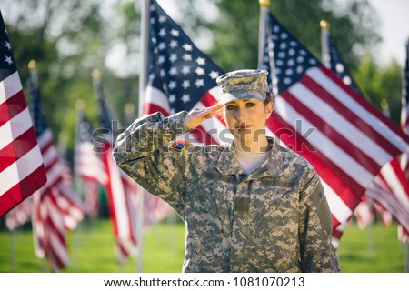 Hispanic American Female Soldier in uniform saluting in front of American flags