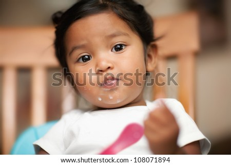 Hispanic baby girl learning to eat by herself with milk spilled on her mouth