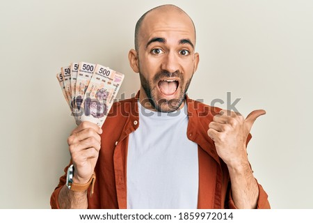 Hispanic bald man holding 500 mexican pesos banknotes screaming proud, celebrating victory and success very excited with raised arm  Foto stock ©