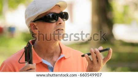 Hispanic blind man with disability. Visually impaired man using Digital Assistant and Ease of Access functions on mobile phone, voice typing to smartphone