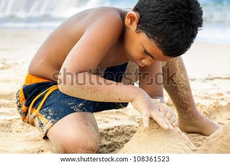 Hispanic boy building a sand castle at a beautiful tropical beach - stock photo