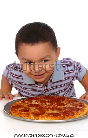 Hispanic boy ready to eat a pepperoni pizza