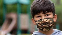 Hispanic boy wearing mask with playground in back during coronavirus covid-19 pandemic social distance, stay at home restrictions