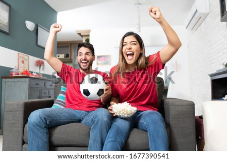Hispanic boyfriend and girlfriend cheering while watching soccer match at home Foto stock ©
