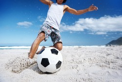 Hispanic Brasil man playing soccer on beach with dribble skill and ball on vacation