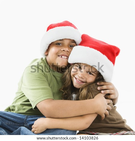 Hispanic brother and sister wearing santa hats hugging
