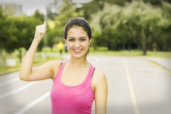 Hispanic brunette in training clothes upper body caption with confident facial expression while holding one arm up.