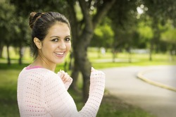 Hispanic brunette model in park wearing white top caption of upper body sideways angle smiling to camera.