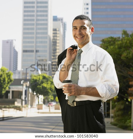 Hispanic businessman holding cup of coffee