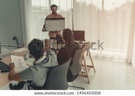 Hispanic businessman holding papers hands and smiling.Young team of coworkers making great business discussion in modern coworking office.Teamwork people concept.Horizontal, blurred background, flares #1496403008