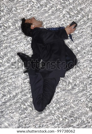 Hispanic businessman jumping and listening to music - stock photo