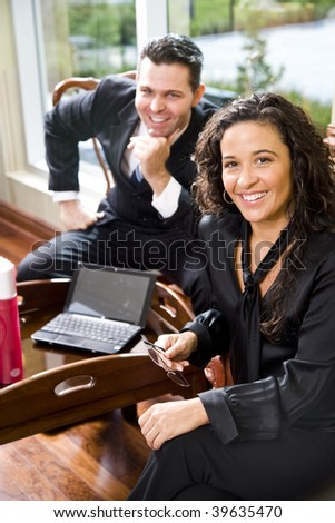 Hispanic businesswoman in office working with male colleague, focus on foreground