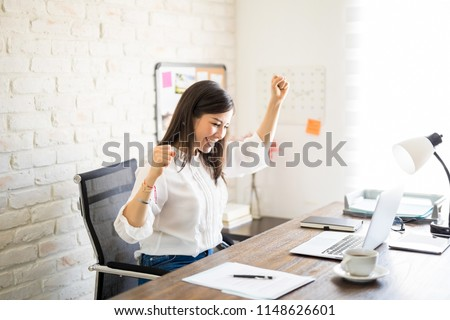 Hispanic businesswoman sitting in front of her desk with arms raised and looking at laptop