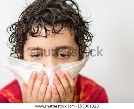 Hispanic child with curly hair suffering from the flu. Kid blowing his nose. Seasonal virus caught by a 7 years old child. He is kept out of school for a few days.