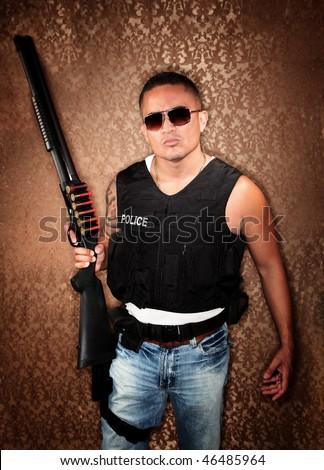 Hispanic Cop Wearing Bulletproof Vest and Holding Shotgun
