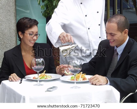 Hispanic couple at a restaurant and a waiter serving.