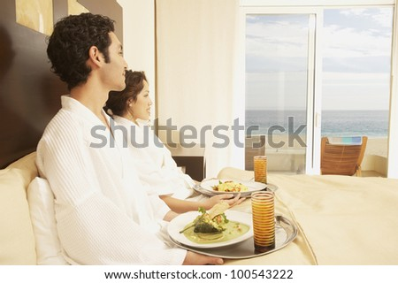 Hispanic couple eating in bed