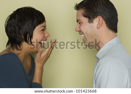 Hispanic couple laughing at each other - stock photo