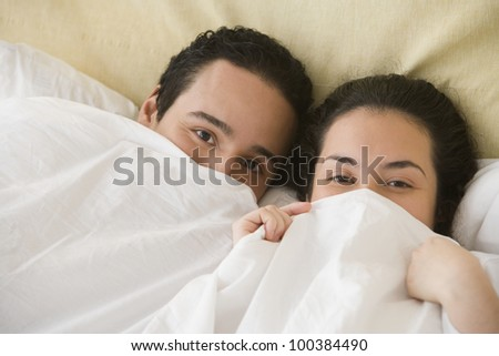 Hispanic couple lying in bed with the sheet pulled up over their noses