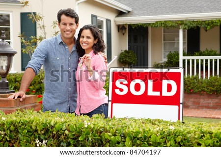 Hispanic couple outside home with sold sign