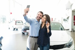 Hispanic couple photographing themselves to post on social media while standing by new car in showroom