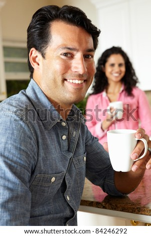 Hispanic couple relaxing in kitchen