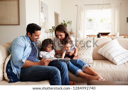 Hispanic couple sitting on the sofa reading a book at home with their baby son and young daughter