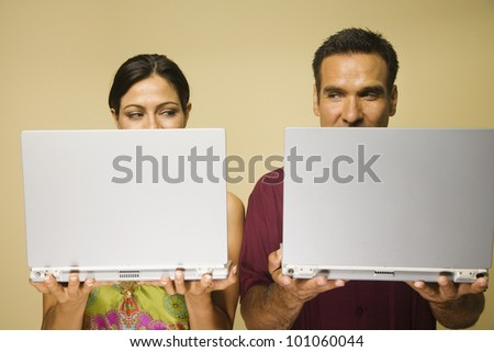 Hispanic couple standing next to each other holding laptops