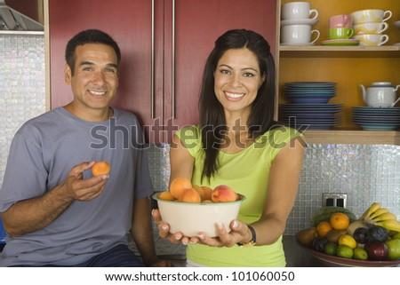 Hispanic couple with bowl of fruit in kitchen