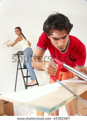 Hispanic couple working at new home.