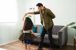 Hispanic dad dancing and listening to music with her little daughter on the living room. Adorable girl twirling with her father and playing at home