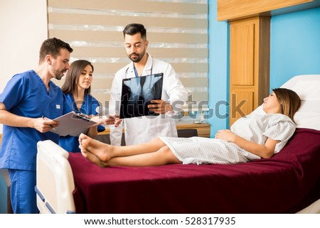Hispanic doctor and a couple of medical interns looking at the x-rays of a female patient in a hospital room