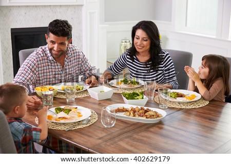 Hispanic Family Enjoying Meal At Table