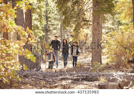 Hispanic Family Of Four Walking Together In A Forest 437135983