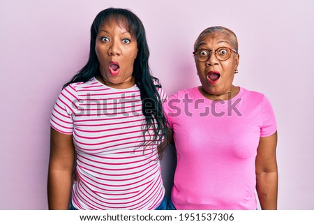 Hispanic family of mother and daughter hugging together with love scared and amazed with open mouth for surprise, disbelief face  Photo stock ©