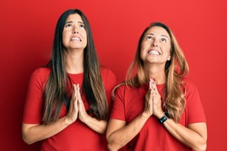 Hispanic family of mother and daughter wearing casual clothes over red background begging and praying with hands together with hope expression on face very emotional and worried. begging.