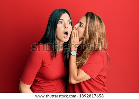 Hispanic family of mother and daughter wearing casual clothes over red background hand on mouth telling secret rumor, whispering malicious talk conversation  Photo stock ©