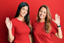 Hispanic family of mother and daughter wearing casual clothes over red background waiving saying hello happy and smiling, friendly welcome gesture