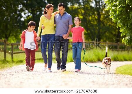 Shutterstock Hispanic Family Taking Dog For Walk In Countryside