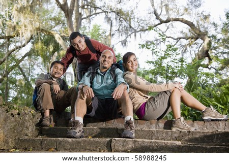 Hispanic family with backpacks hiking in park resting