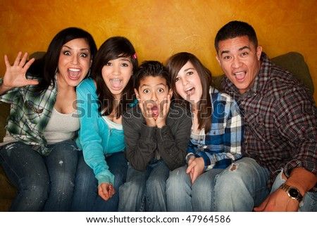 Hispanic Family with Big facial Reactions Sitting on Couch