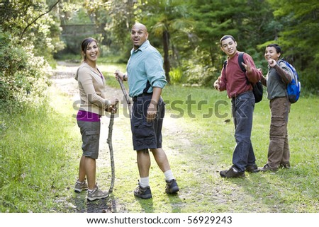 Hispanic family with two boys hiking in woods on trail