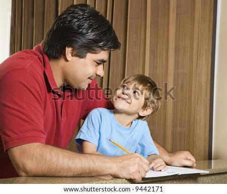 Hispanic father and   son doing homework and making eye contact.