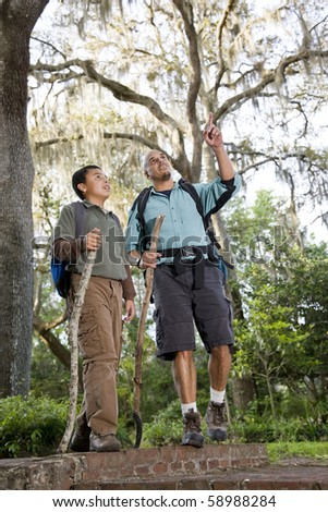 Hispanic father and son hiking in park enjoying nature