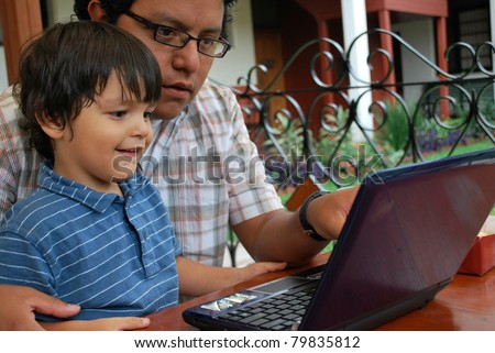 Hispanic father and son on the computer