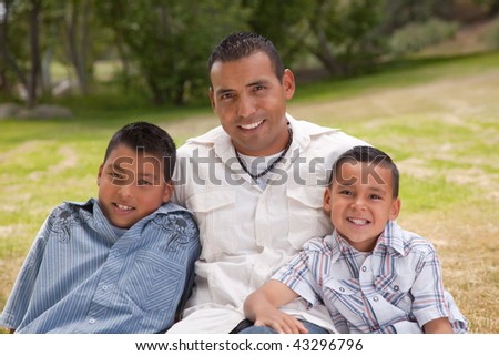 Hispanic Father and Sons Portrait in the Park.