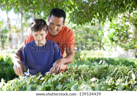Hispanic father happily teaches his teenaged son how to use hedge clippers to trim bushes in lush yard.