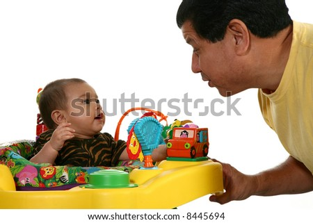 Hispanic father playing with baby girl and toys over white.