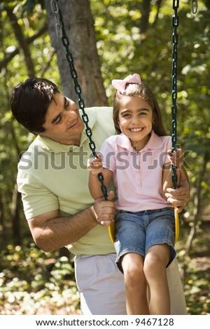 Hispanic father pushing daughter on swing.